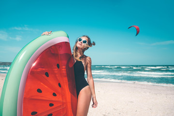 Model with watermelon lilo at the beach
