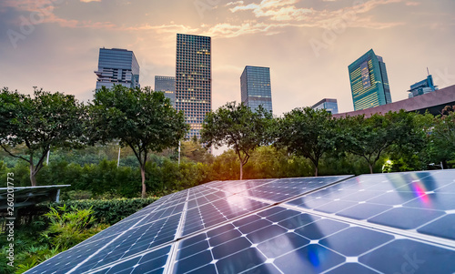 Photo Ecological energy renewable solar panel plant with urban landscape landmarks