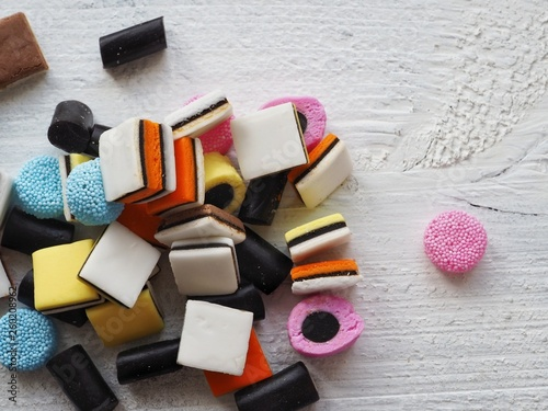 Licorice sweets on white wooden background Wallpaper Mural