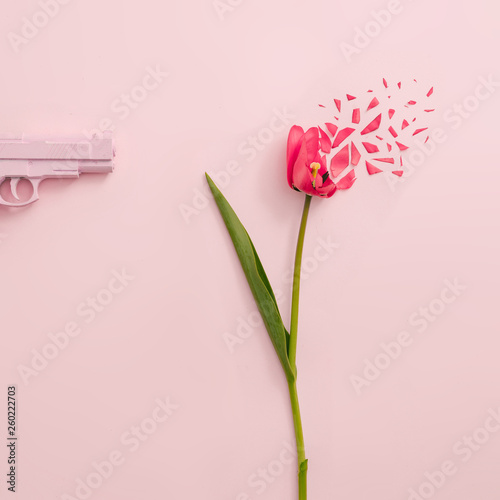 Creative concept made with pink gun and red tulip flower exploding on pastel pink background. Minimal nature composition with copy space. Wall mural