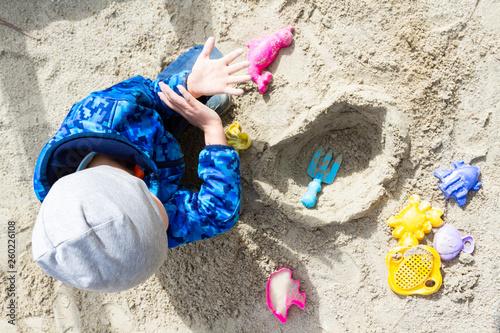 Boy child playing in sandbox at playground top view Canvas Print
