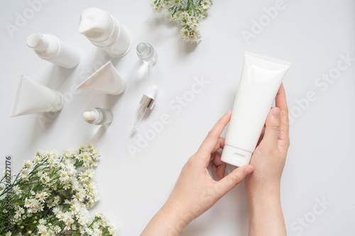 Fotomural Young female hand holding blank white squeeze bottle plastic tube w/ organic natural skincare products and flower on white table
