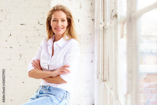 Obraz na plátně Attractive mature woman with toothy smile relaxing at the window