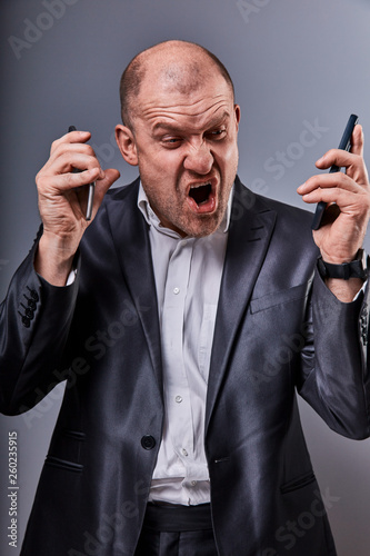 Unhappy loud crying anger business man talking on two mobile phones very emotional in office suit on grey studio background Fototapet