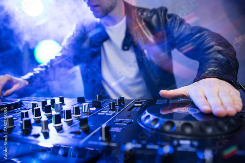 Dj mixing at party festival with red light and smoke in background - Summer nightlife view of disco club inside Canvas Print