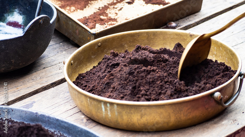 Fotografía  Coffee powder that has been crushed Put in a brass container And having a spoon to scoop it up