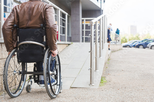 Photo  Man in a wheelchair use a wheelchair ramp.
