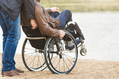 Valokuva  Young man in wheelchair with his assistant on a stroll through the park