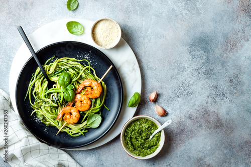 Photo  Zucchini spaghetti with pesto sauce and grilled shrimp skewers