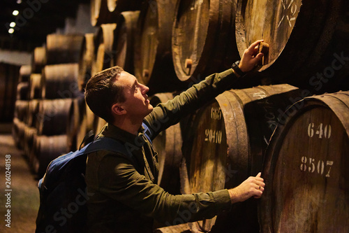 Young man tourist  walk in old aged traditional wooden barrels with wine in a va Canvas Print