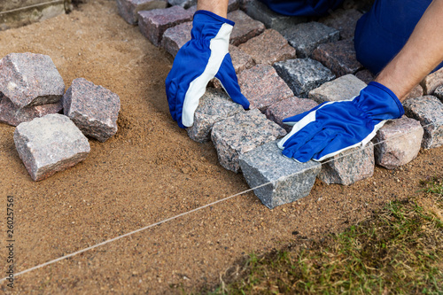 Fototapeta cobblestone installation - paver laying granite stone pavers
