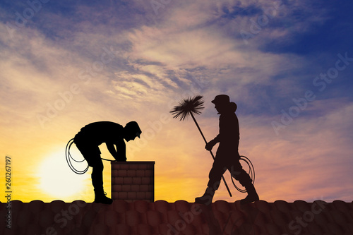 Fotografiet illustration of chimney sweep on the roof at sunset