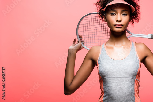 african american sportswoman in sun visor holding tennis racket and looking at c Wallpaper Mural