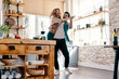 Leinwanddruck Bild - Playful. Full length of beautiful young couple in casual clothing dancing and smiling while standing in the kitchen at home