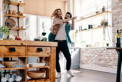 Obraz Playful. Full length of beautiful young couple in casual clothing dancing and smiling while standing in the kitchen at home - fototapety do salonu