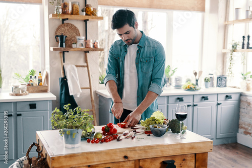Homemade dinner. Handsome young man in casual wear cutting vegetables while standing in the kitchen at home