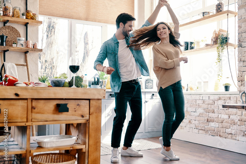 Two hearts filled with love. Full length of beautiful young couple in casual clothing dancing and smiling while standing in the kitchen at home - 260296122