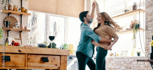 Obraz Simple joy of loving. Full length of beautiful young couple in casual clothing dancing and smiling while standing in the kitchen at home - fototapety do salonu