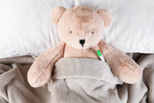 Toy Bear With Thermometer Lying In Bed, Top View. Children's Hospital