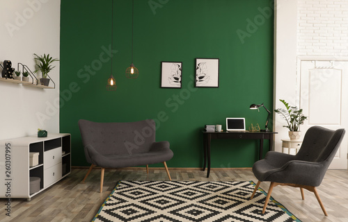 Valokuva  Modern living room interior with workplace near green wall