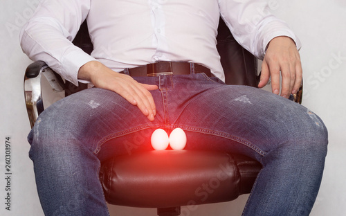 Photo A man in a white shirt is sitting on a chair with a cyst of the epididymis of th