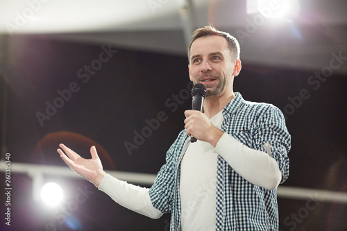 Obraz na plátně  Waist up portrait of mature man giving speech standing on stage in spotlight and