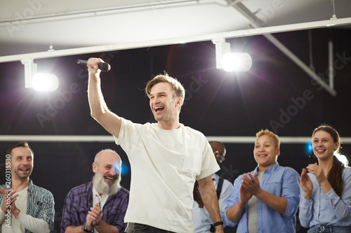 Fotografie, Obraz  Portrait of excited young man holding microphone standing on stage in spotlight