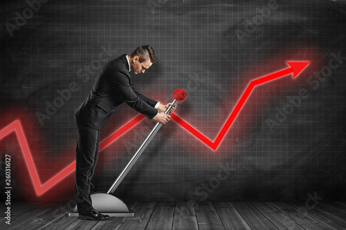 Fotomural Side view of businessman looking down and pulling big lever near black graph ruled wall with red graph arrow on it