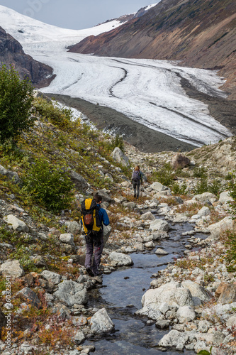 Valokuva  Man and woman walking along small stream toward Berendon Glacier in British Colu