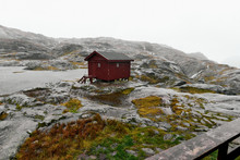 Remote Isolated Red Wooden Cabin In The Rocky Mountains On Lofoten In Norway Next To A Lake During A Heavy Storm And Rain.