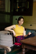 Asian chinese girl having a good time at a coffee shop in hangzhou, China. wearing a yellow tank top and a reddish patterned dress with pants. holding a hand bag