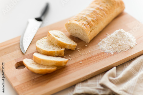 food, junk-food and unhealthy eating concept - close up of white ciabatta bread on wooden cutting board, knife and kitchen towel