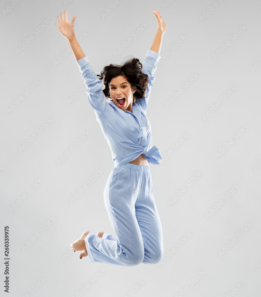 Fototapety, obrazy: fun, people and bedtime concept - happy young woman full of energy in blue pajama jumping over grey background