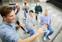 Positive Successful Business Coach In Casual Shirt Gesturing Hand And Speaking Into Microphone While Presenting Sales Strategy At Conference