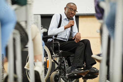 Obraz Serious confident motivational disabled mature African-American speaker in glasses sitting in wheelchair and looking at audience while saying speech into microphone at conference - fototapety do salonu