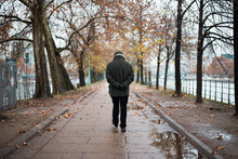 Old Man Walking Away,following The Path On A Rainy Autumn Day