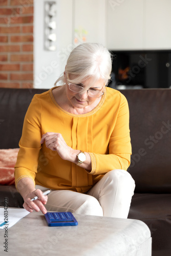 Senior woman with calculator and bills counting - 260342903