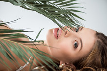 Attractive Young Woman Lying Near Tropical Palm Leaves On White