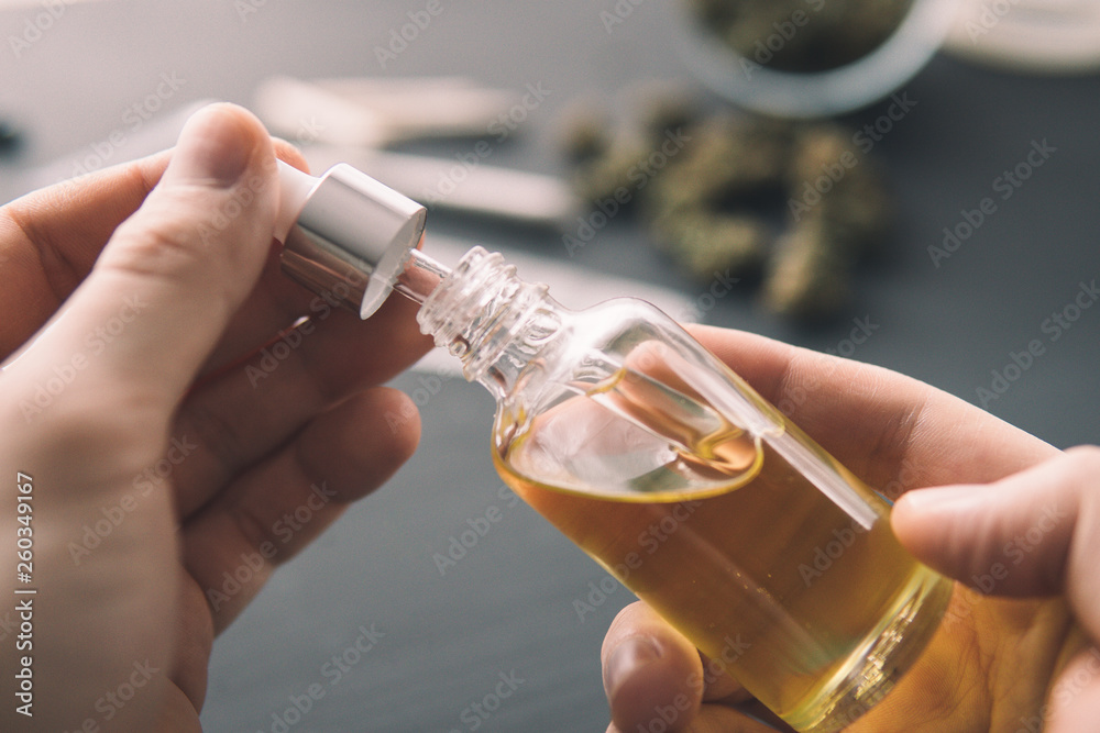 Fototapety, obrazy: hemp product, Hand holding bottle of Cannabis oil in pipette, close up, natural herb, medical marijuana concept, CBD cannabis OIL.