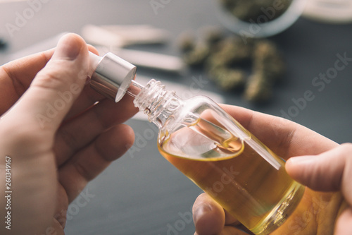 Fotografia  hemp product, Hand holding bottle of Cannabis oil in pipette, close up, natural herb, medical marijuana concept, CBD cannabis OIL