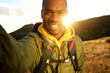 happy black man hiking and taking selfie with sunset in background