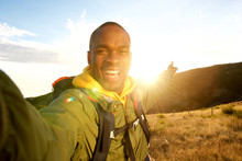 Happy Young Black Man Hiking With Backpack Taking Selfie And Pointing To Sunset