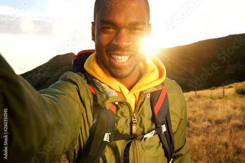 Photo  happy black man hiking and taking selfie with sunset in background