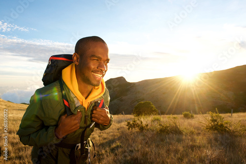 Foto auf Leinwand Honig young black man walking with backpack in mountains with sunrise in background