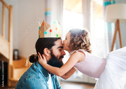 Photographie A side view of small girl with a princess crown and young father at home, playing