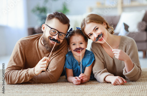 happy funny family mother father and child daughter with mustache on stick