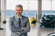 confident salesman standing crossed arms in car dealership showroom
