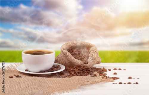 Foto op Plexiglas Cafe Cup of hot coffee with beans on background