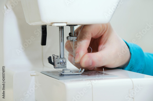 Fotografía  Caucasian girl inserts a thread into the needle of the sewing machine