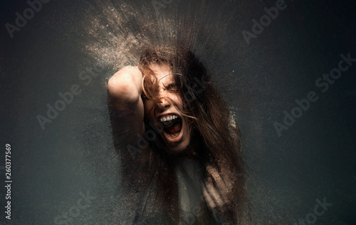 Fotografía  Screaming crazy frustrated woman dispersing into million particles, anxiety, ang